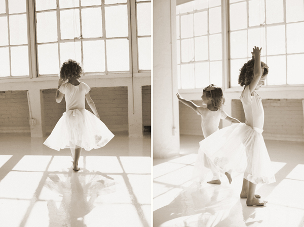 Two sisters dancing in tutus next to a window
