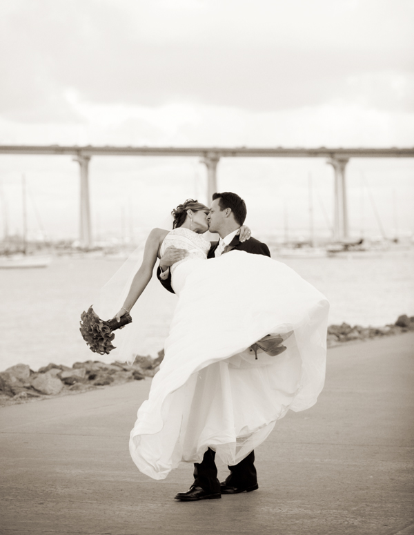 black & white photography of  bride and groom kissing by the coronado bridge in San Diego back bay