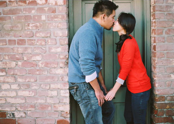 a couple kissing in front of a green door